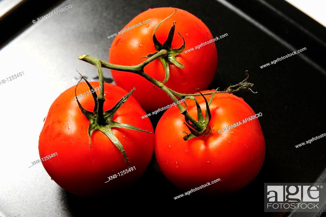 Stock Photo: Red tomatoes photographed on black slightly backlit.