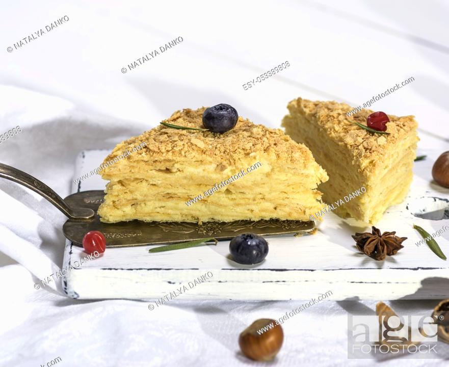 Stock Photo: two baked cakes Napoleon with cream on a white wooden board, close up.