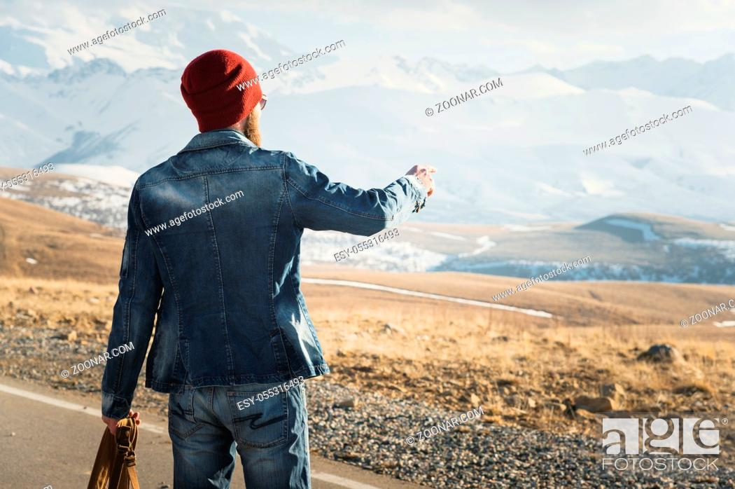 Photo de stock: Tourism and people concept - stylish hipster walking along country road outdoors and pointing finger to something.