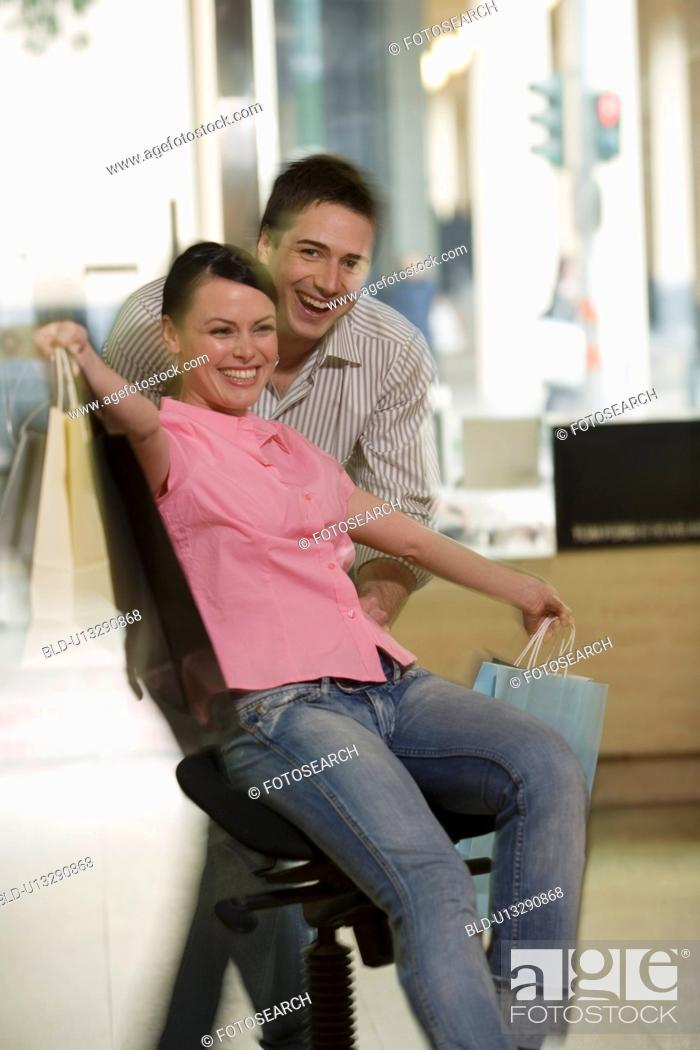 Stock Photo: Happy couple posing with shopping bags in a sunglasses store.