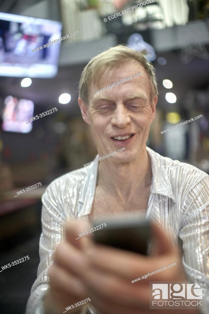 Stock Photo: Eccentric man in cafe, using phone. London, England.