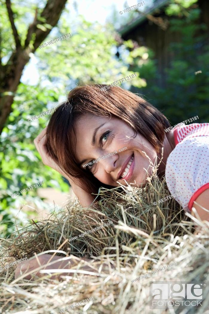 Stock Photo: Germany, Bavaria, Woman lying in hay, smiling, portrait.