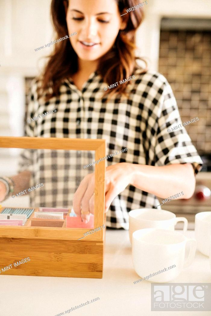 Stock Photo: Woman with long brown hair, wearing a chequered shirt, standing in a kitchen, making a cup of tea.