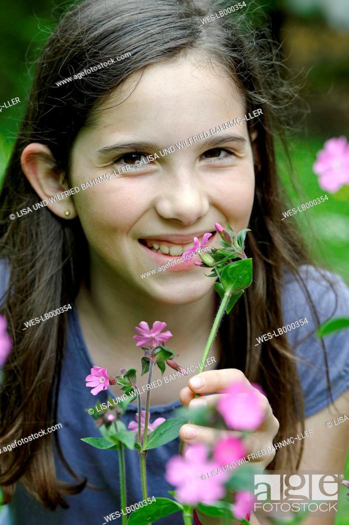 Imagen: Girl smells at a spring flower.