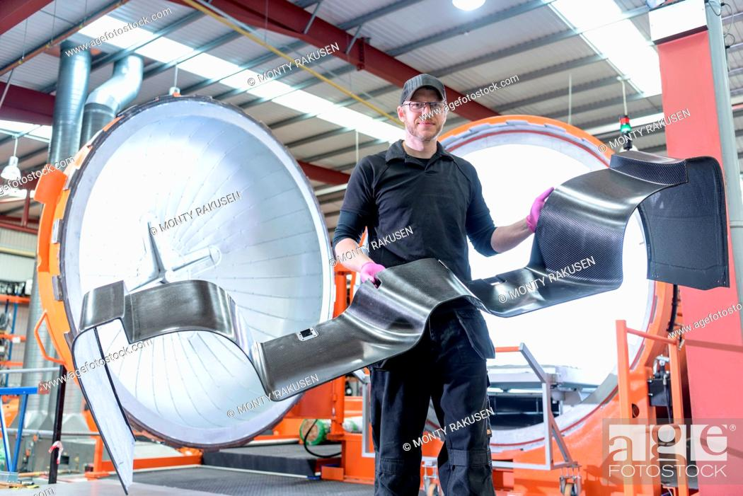 Imagen: Engineer inspecting carbon fibre body part in front of autoclave in racing car factory.