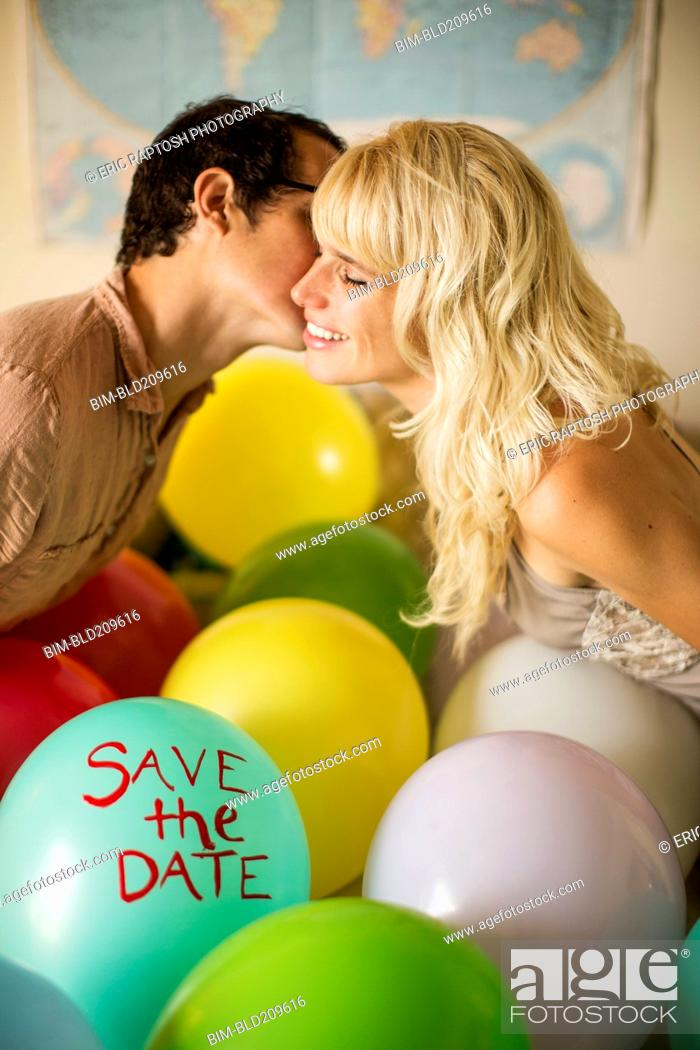 Stock Photo: Caucasian couple kissing over balloon with 'save the date text.