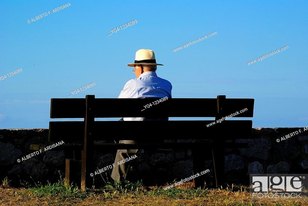 Stock Photo: Man sitting on a bench in the Paseo de San Pedro, Llanes, Asturias.