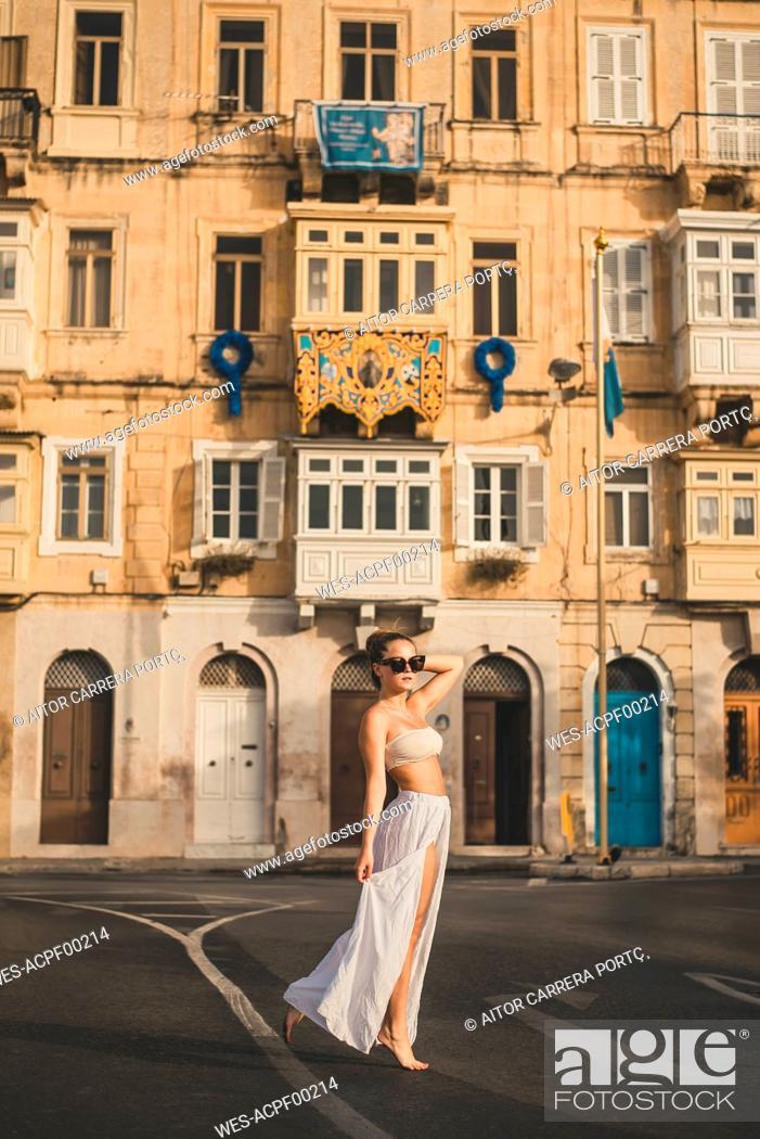 Stock Photo: Teenage girl weraing long skirt and bikini top, posing in the street.