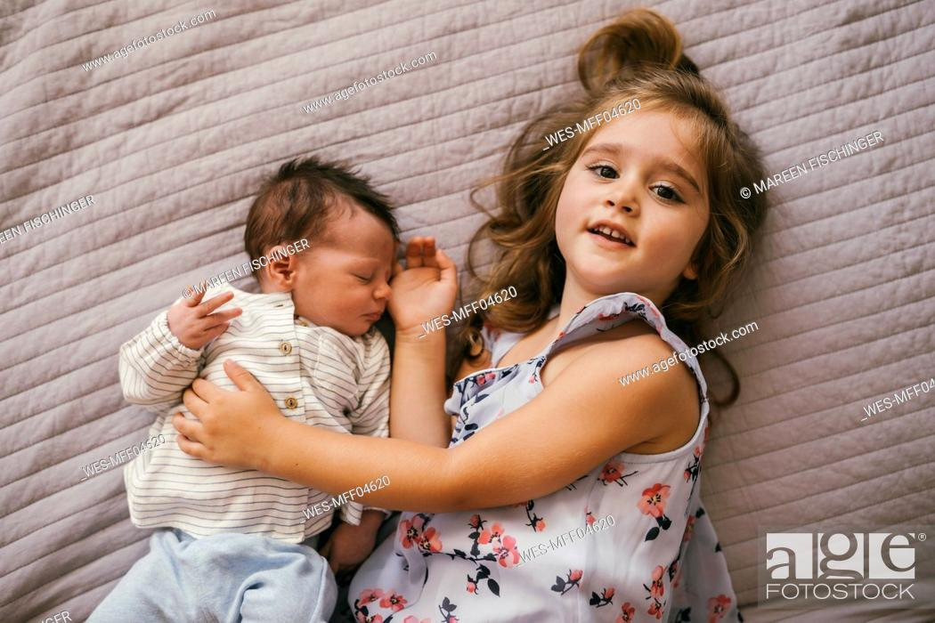 Stock Photo: Smiling girl lying on blanket cuddling with her baby brother.