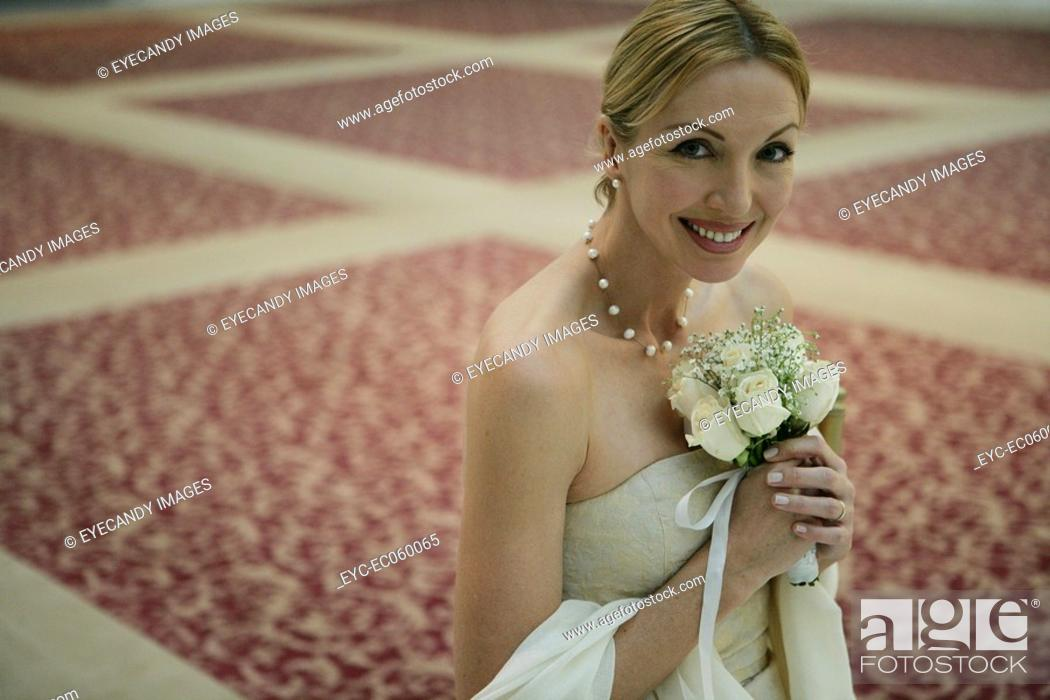 Stock Photo: Mature woman holding a bouquet smiling.