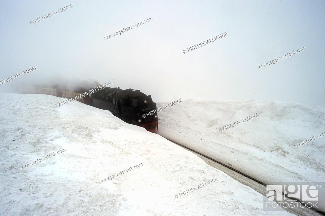 Stock Photo: 07 February 2019, Saxony-Anhalt, Brocken: The Brockenbahn of the Harzer Schmalspurbahnen (HSB) travels in the fog between two metres high snow drifts.