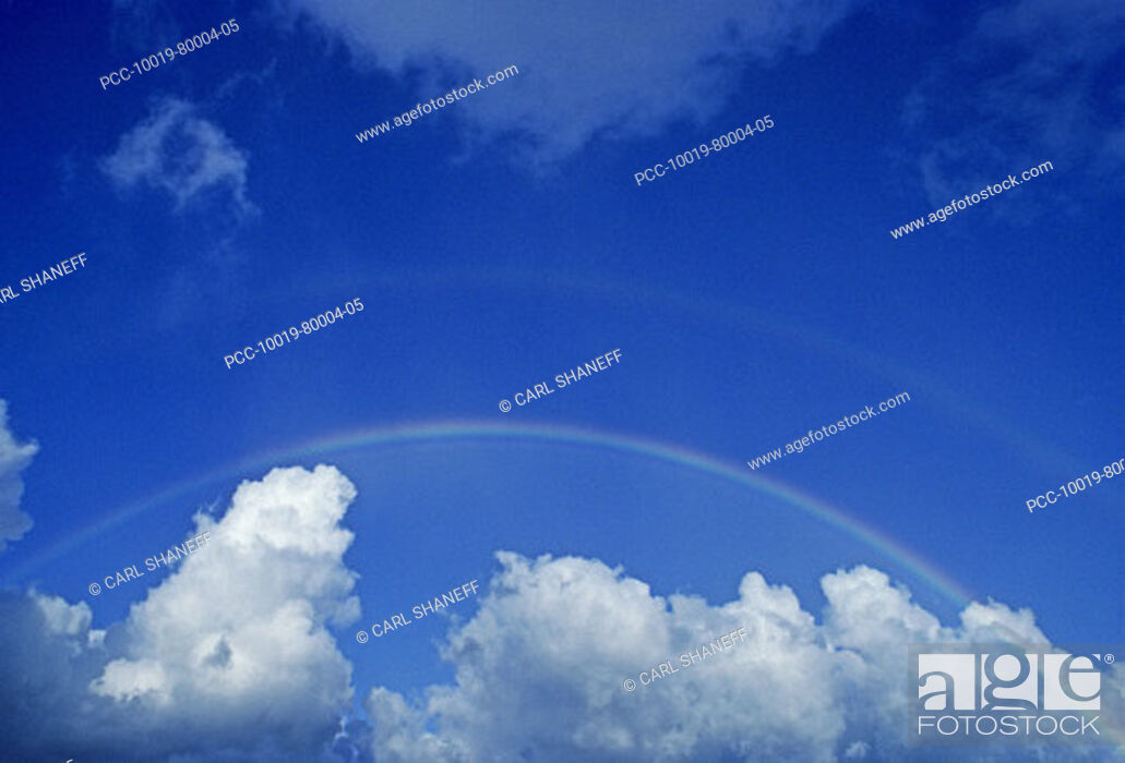Stock Photo: Hawaii, Rainbow arching over clouds in blue sky.