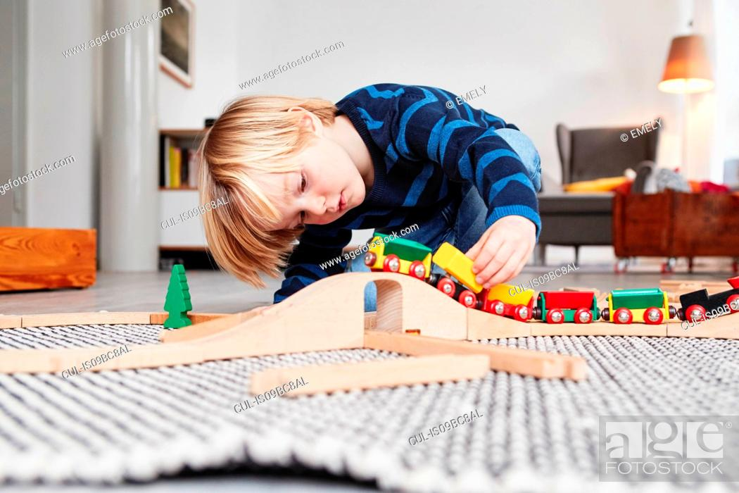 Stock Photo: Young boy playing with toy train and track.