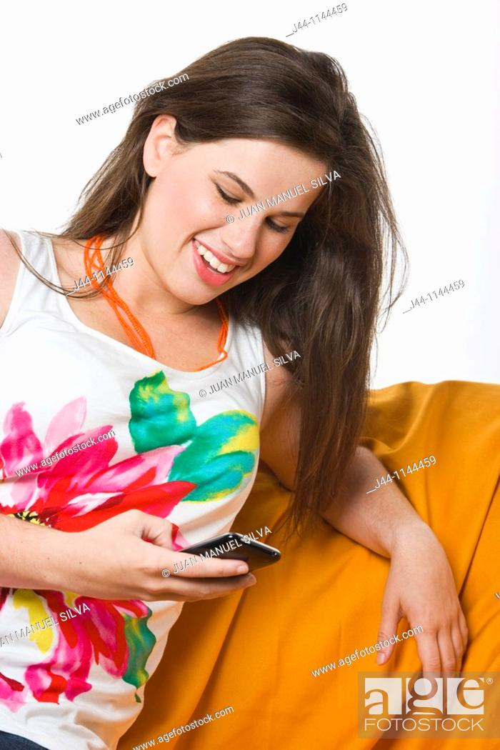 Stock Photo: Young woman using mobile phone sitting on sofa smiling.
