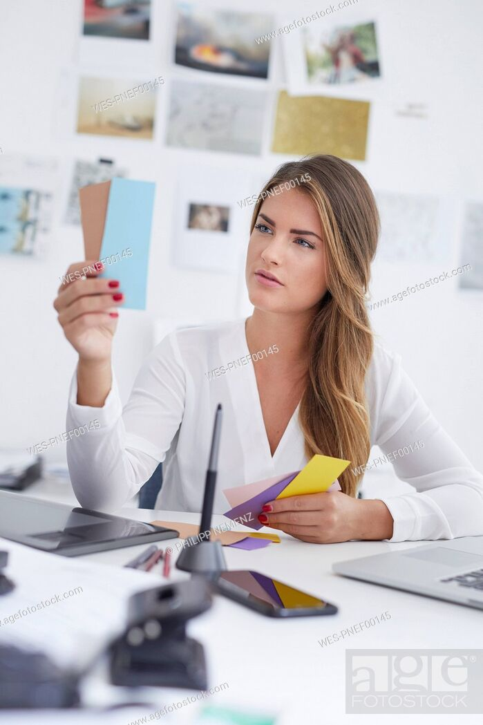 Stock Photo: Young woman looking at notes at desk in office.