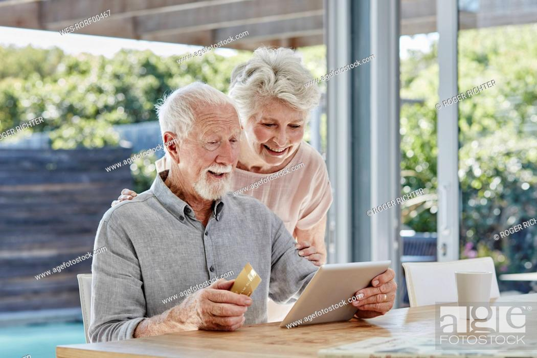 Stock Photo: Senior couple doing online payment with credit card.
