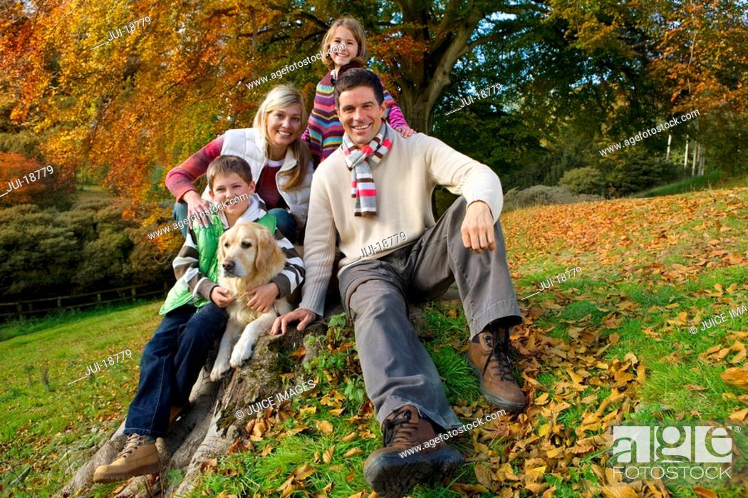 Stock Photo: Portrait of family and dog sitting on tree stump in woods.