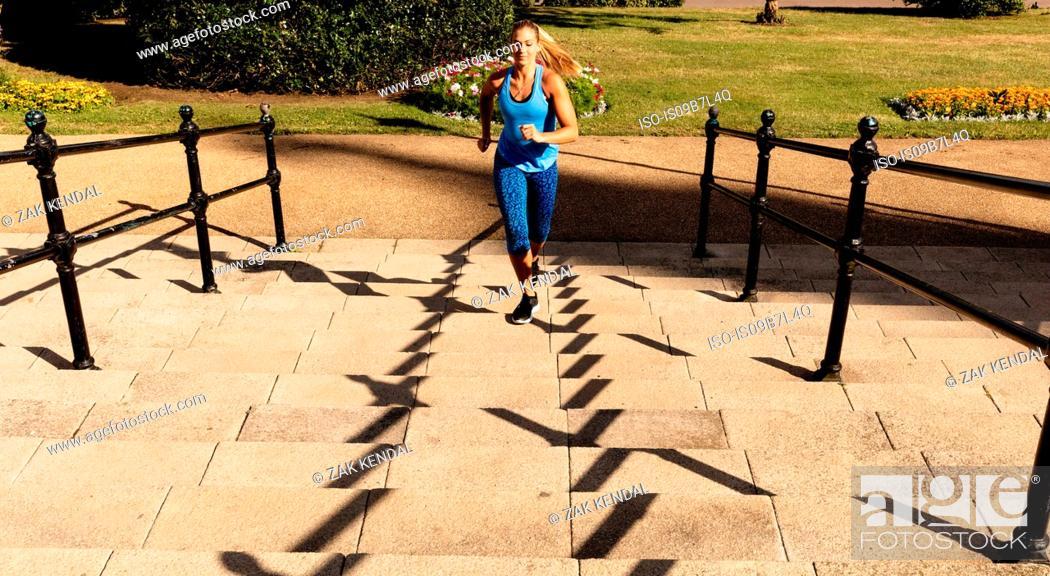 Stock Photo: Young female runner running up park stairway.