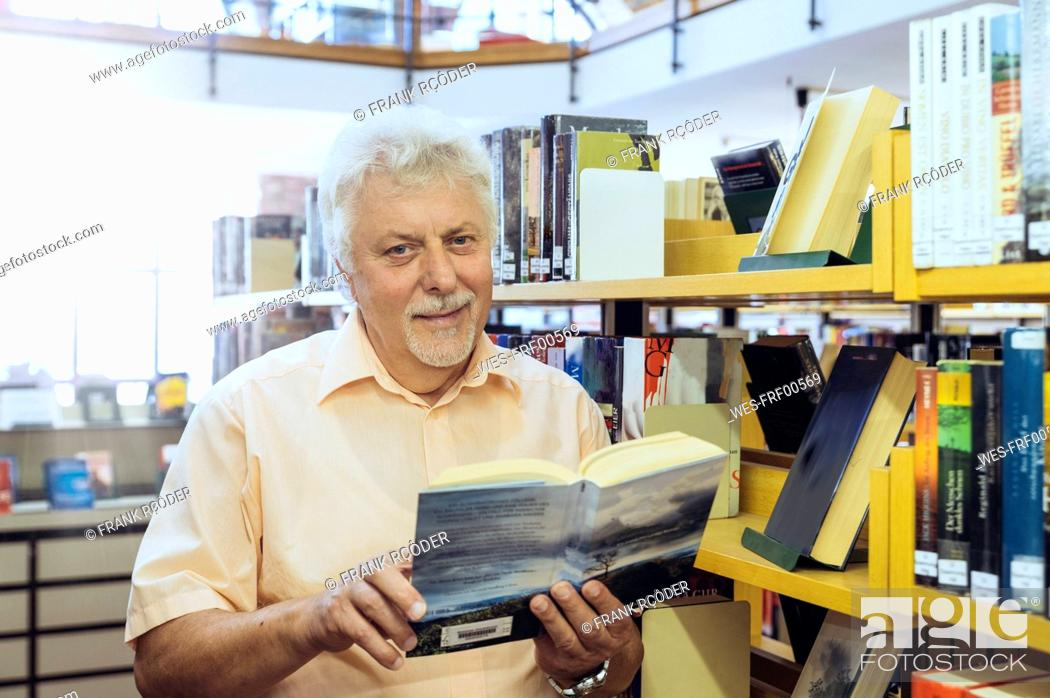 Stock Photo: Portrait of senior man in a city library holding book.