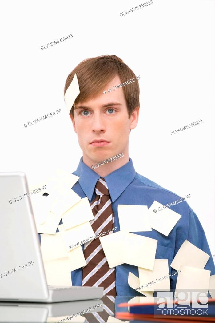 Stock Photo: Businessman working on a laptop and covering with adhesive notes.