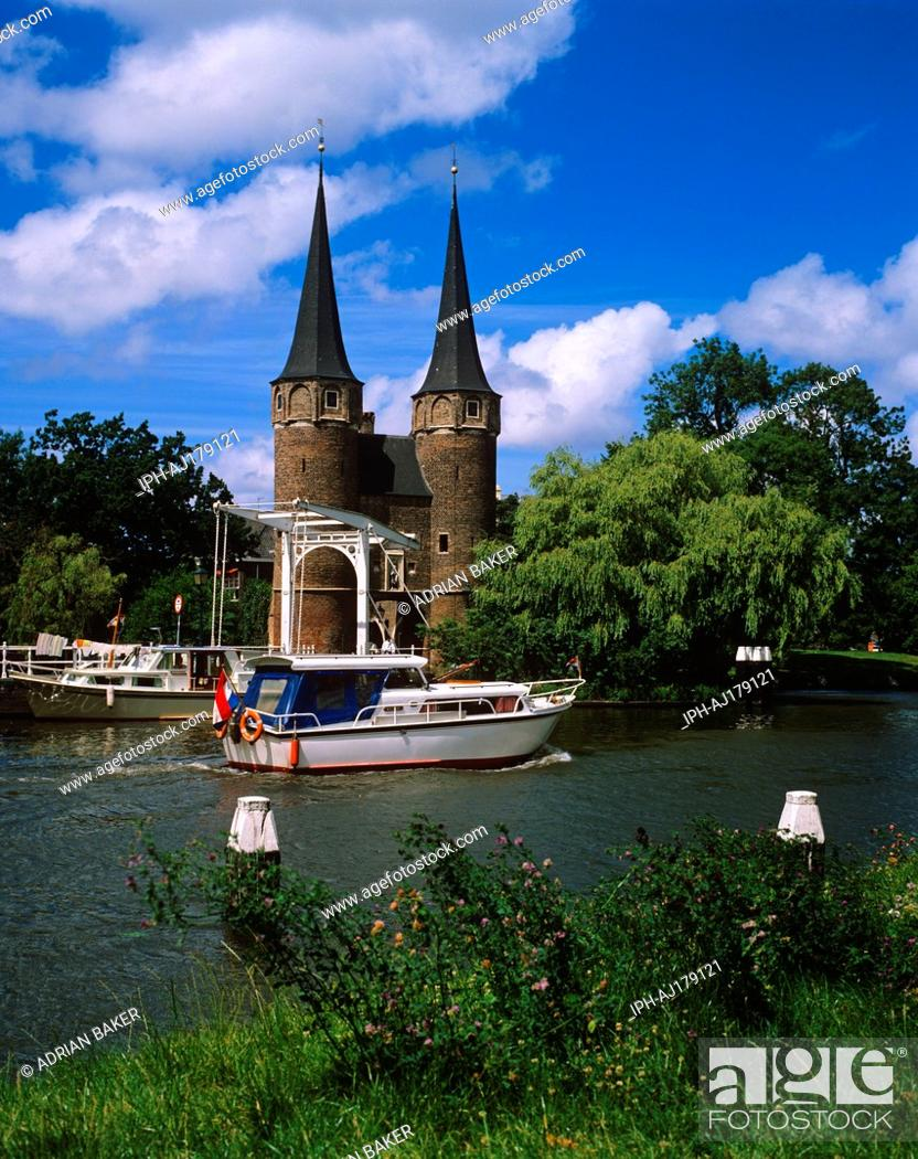 Stock Photo: Boat on the canal passing the Eastern Gate Oostpoort, Last of the ancient gateways into the city of Delft.