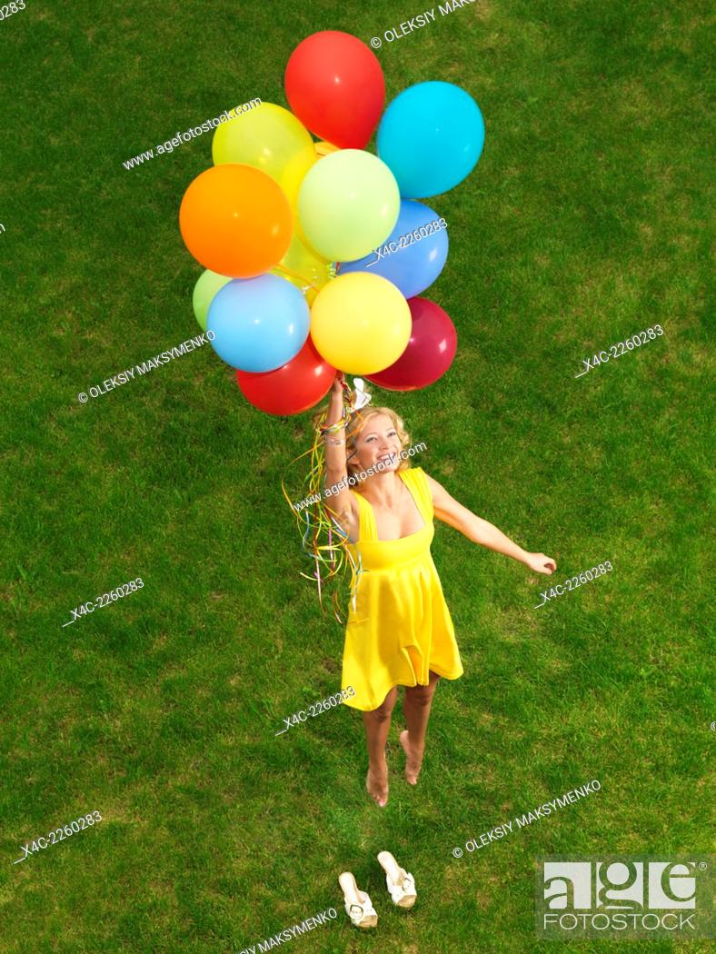 Stock Photo: Young happy woman flying up from the ground on colorful air balloons.