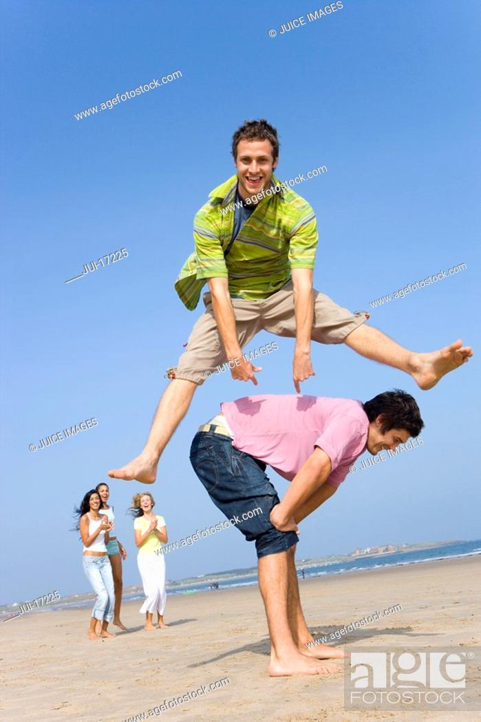 Stock Photo: Young man leaping over friend at beach.