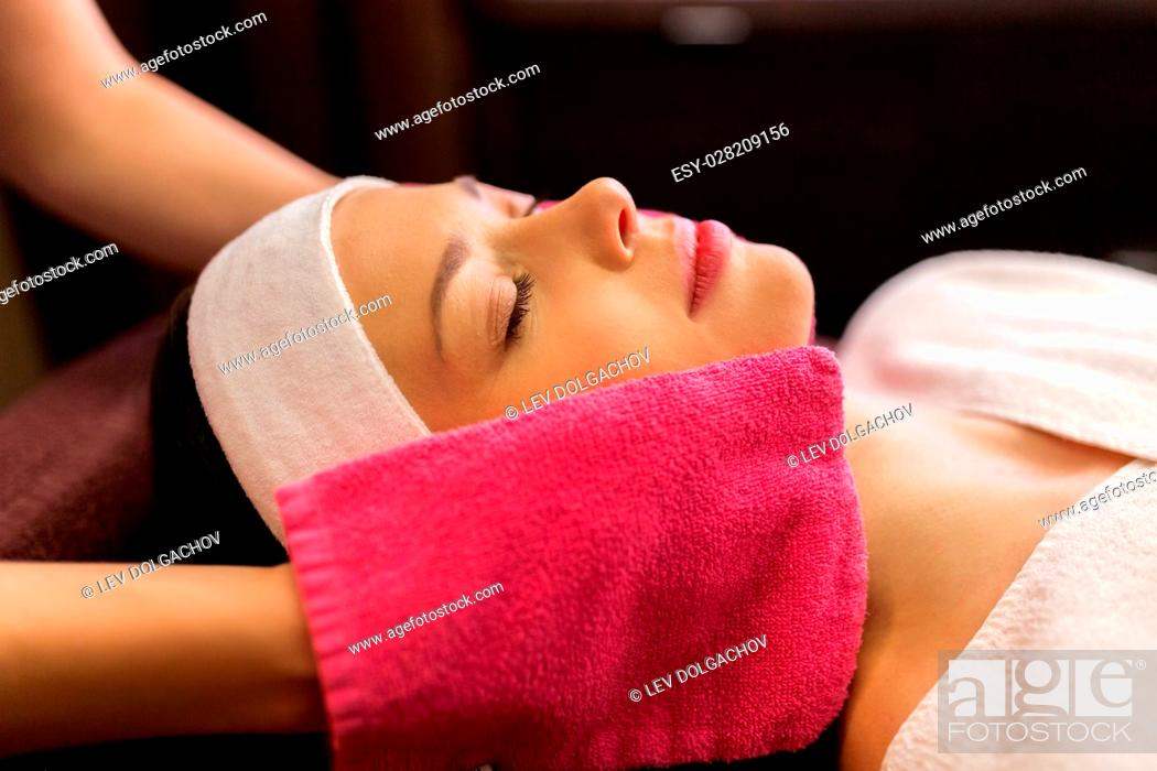 Stock Photo: people, beauty, lifestyle and relaxation concept - beautiful young woman lying with closed eyes and having face massage with terry gloves at spa.