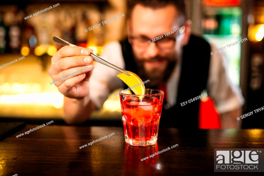 Stock Photo: Bartender behind bar counter making alcohol coctail in restaurant.