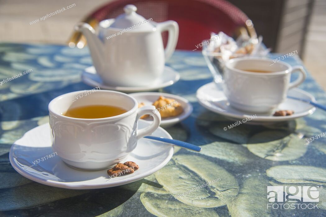 Stock Photo: Two cups of tea with biscuits in a terrace.