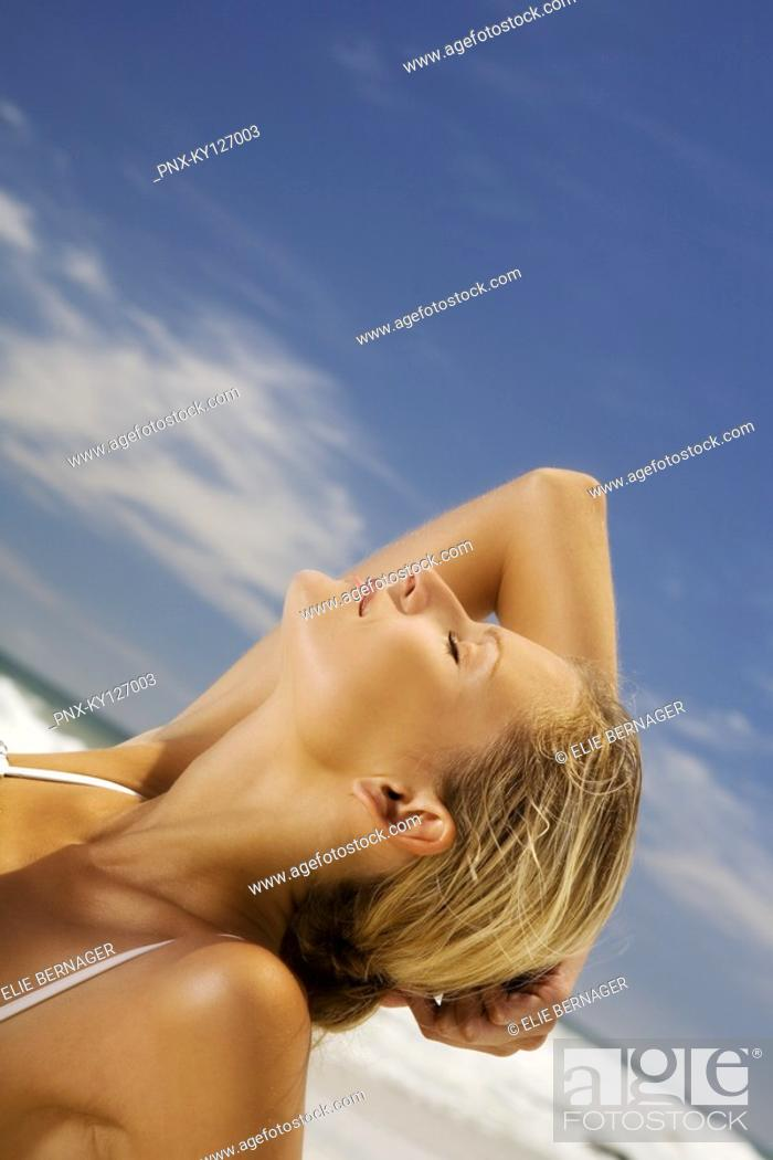 Stock Photo: Young woman lying on beach, head back.