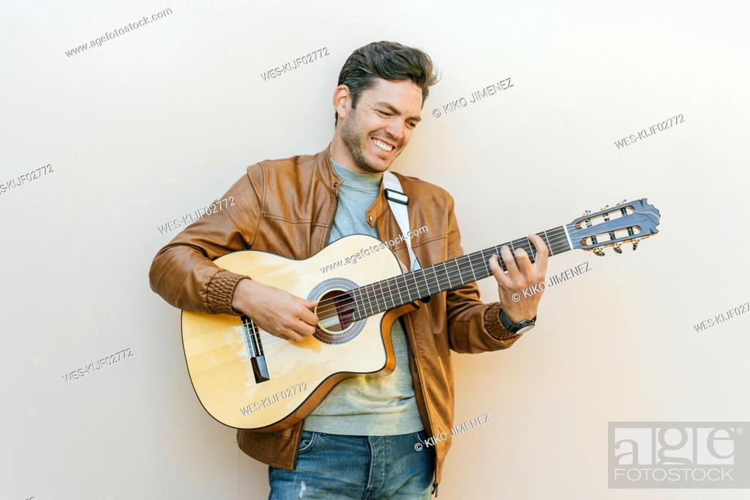 Stock Photo: Smiling man playing guitar in front of a wall.