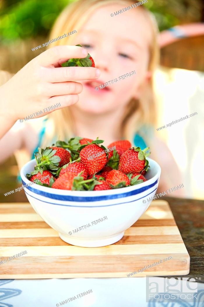 Stock Photo: Girl eating stawberries form bowl.