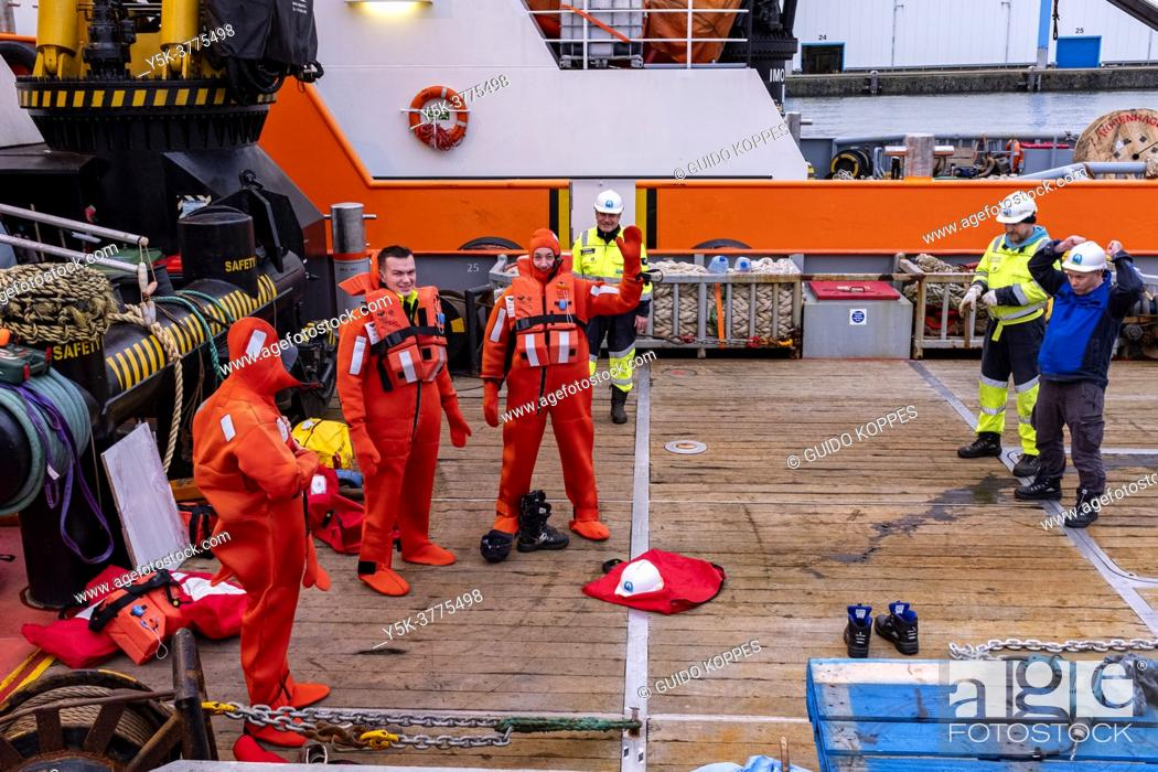 Stock Photo: Rotterdam, Netherlands. Groups of SeaMen on Deck of a Thug, buzy with their training in Emergancy Procedures.