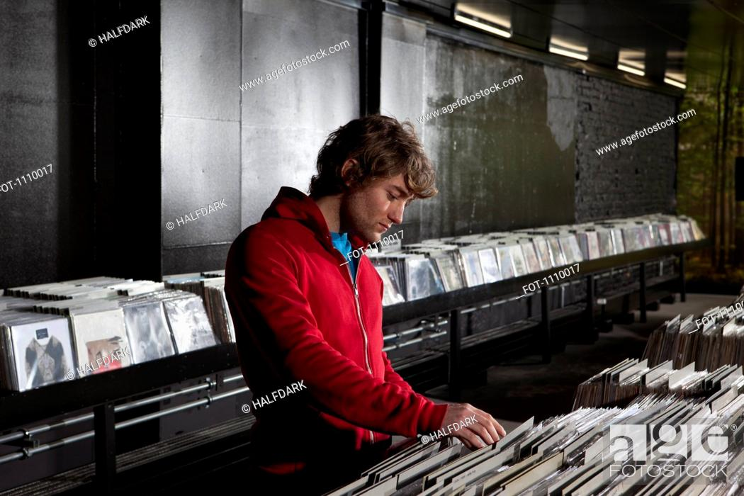 Stock Photo: A young man looking through records at a record store.