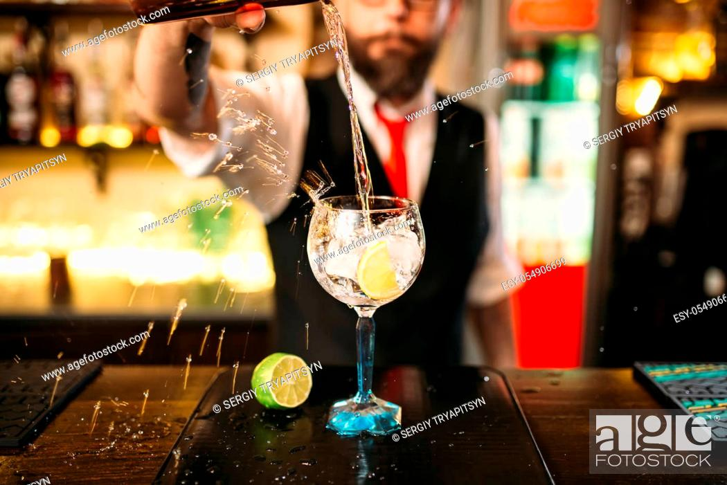 Stock Photo: Bartender pouring alcoholic drink in glass. Barman flairing with alcoholic cocktail.