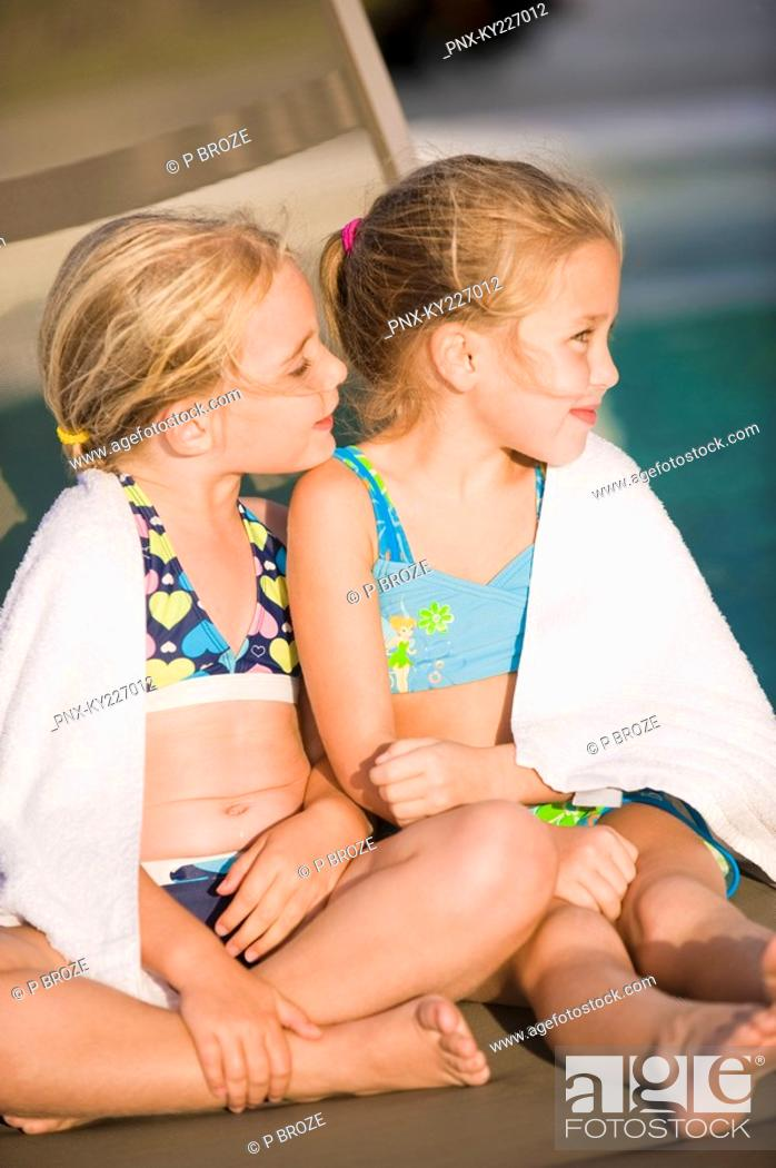 Stock Photo: Two girls sitting on a lounge chair at the poolside.