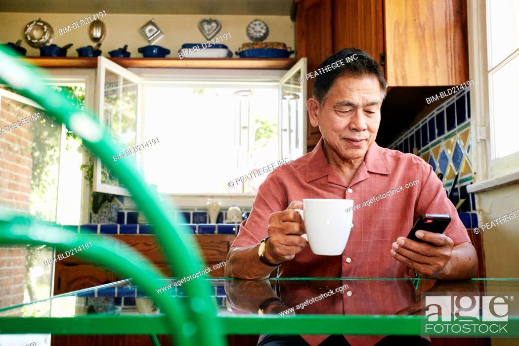Stock Photo: Filipino man using cell phone in kitchen.