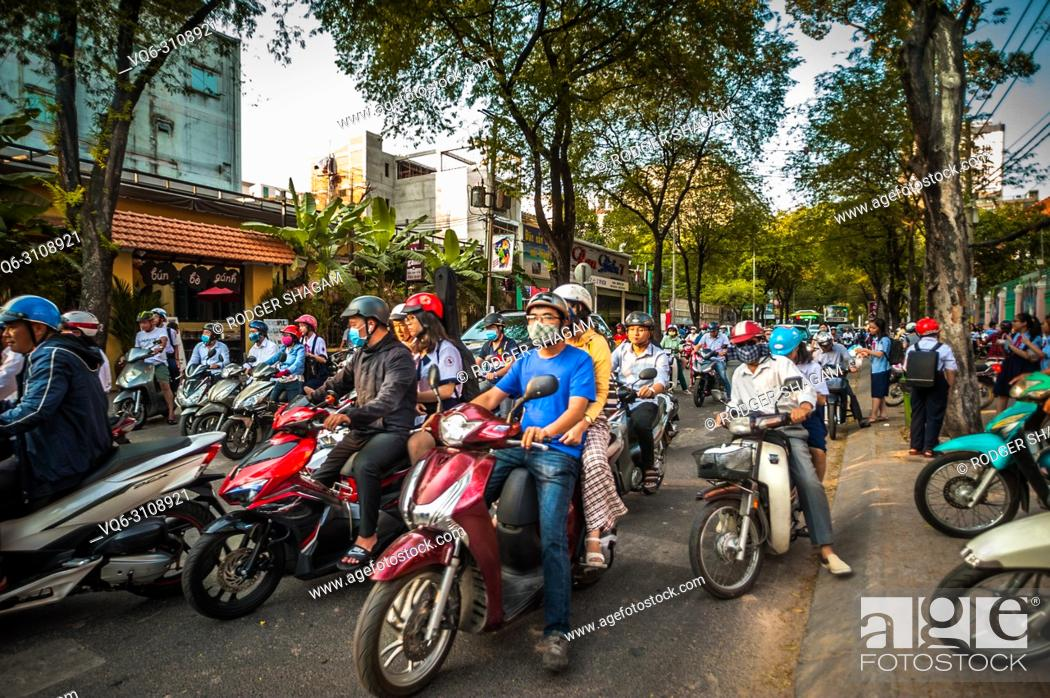 Stock Photo: Some of the millions of motorcyclrs that travel around Saigon (Ho Chi Minh City) daily. Vietnam.