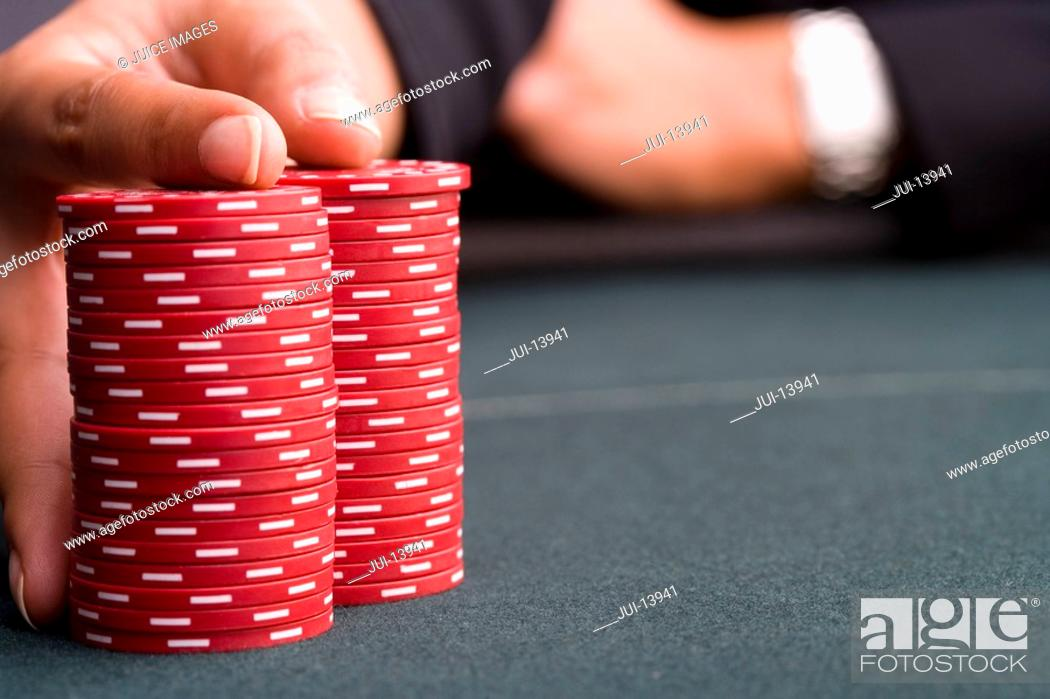 Stock Photo: Woman with hand on pile of gambling chips, close-up.