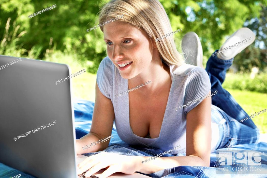 Stock Photo: Germany, Cologne, Young woman using laptop in meadow, smiling.