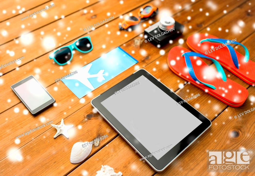 Stock Photo: travel, tourism, technology and winter holidays concept - tablet pc computer, airplane ticket and beach stuff over snow.
