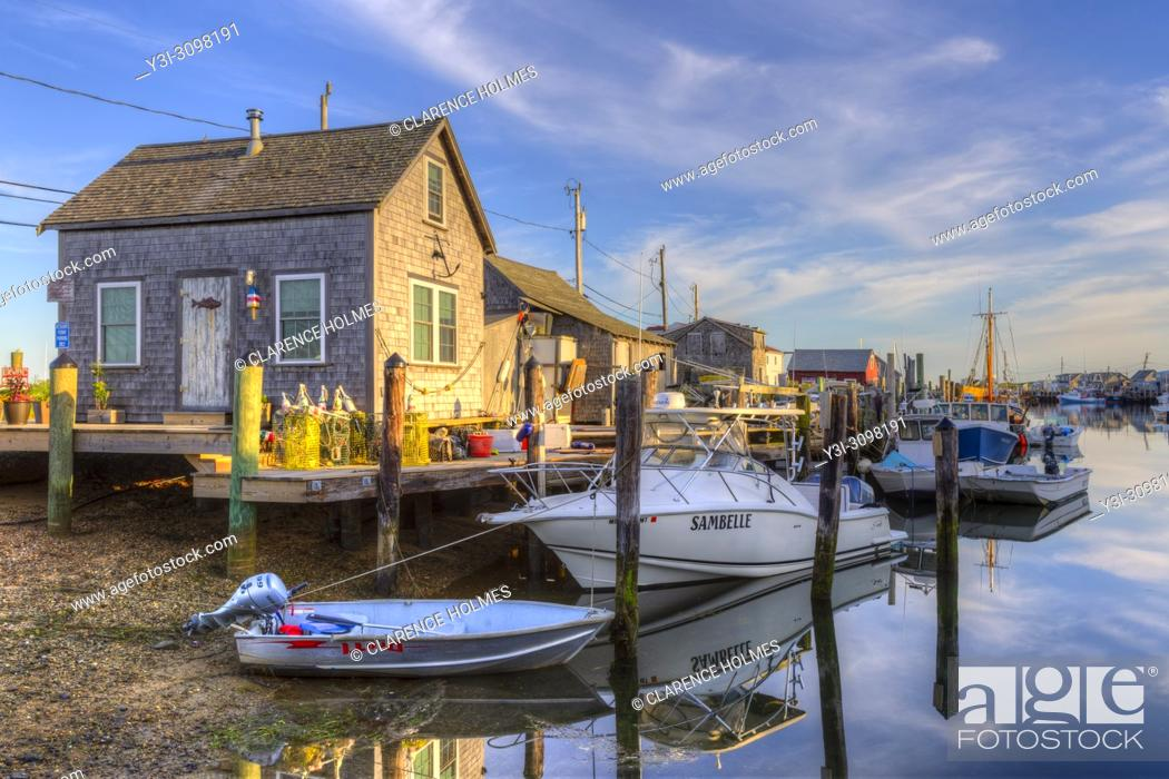 Stock Photo: The commercial fishing village of Menemsha and boats docked in Menemsha Basin lit by golden light during the first hour after sunrise, in Chilmark.