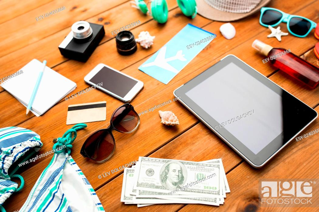 Stock Photo: vacation, tourism, technology and objects concept - close up of tablet pc computer, dollar money and travel stuff.