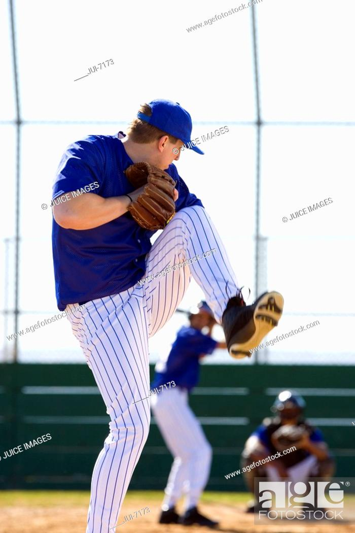 Stock Photo: Young men playing baseball, focus on pitcher about to throw ball in foreground, rear view.