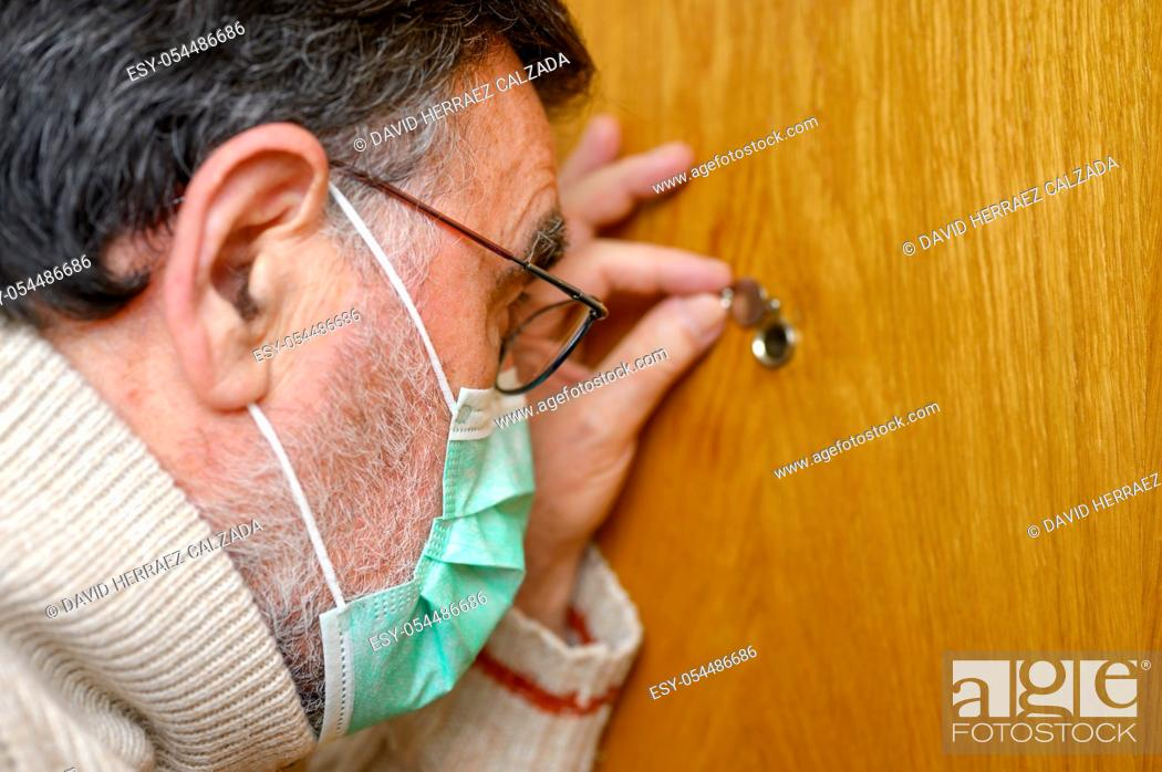 Stock Photo: Covid-19 concept. Stay at home. Self-isolation to prevent the coronavirus pandemic. Senior man in protective green mask looks through the peephole .