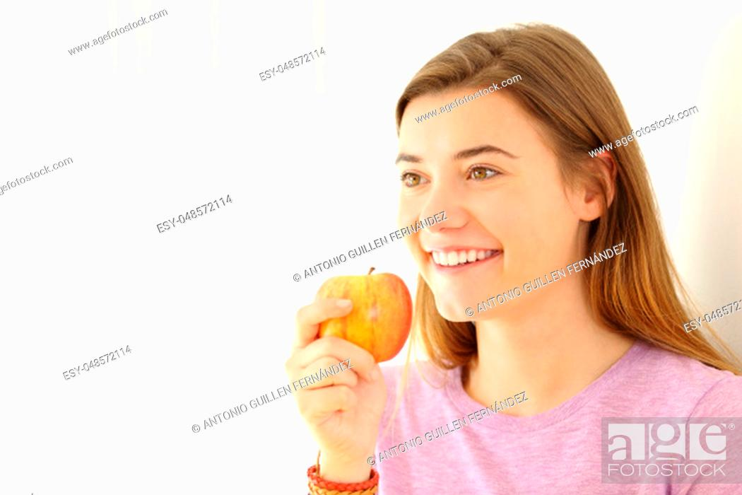 Stock Photo: Happy teen holding an apple looking away on white at side.