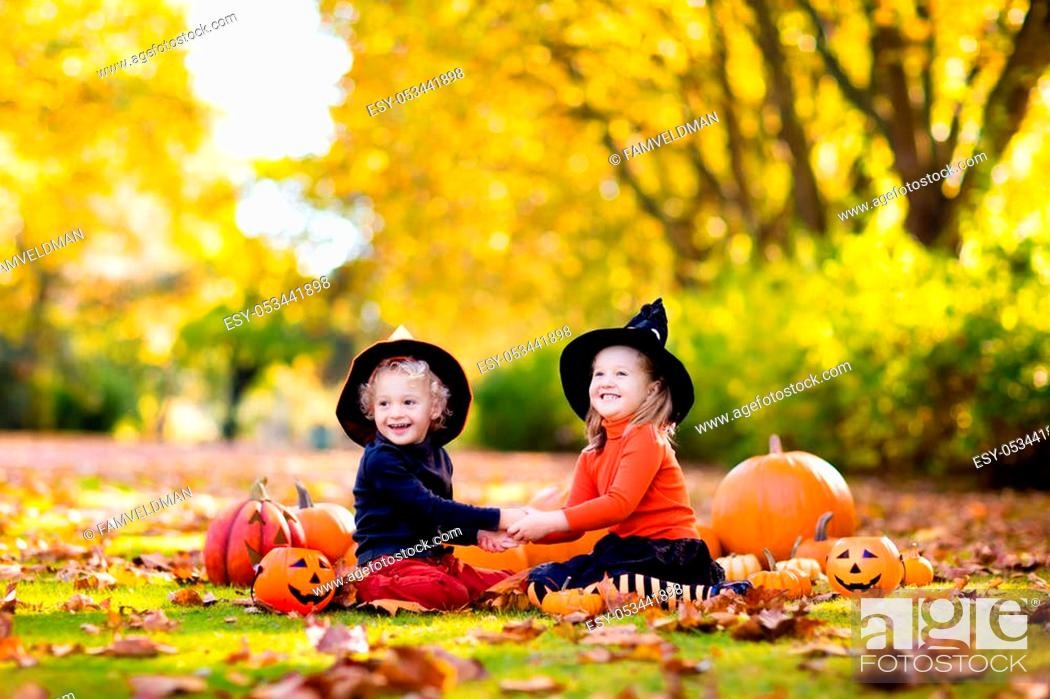 Stock Photo: Children in black and orange witch costume and hat play with pumpkin and spider in autumn park on Halloween. Kids trick or treat.