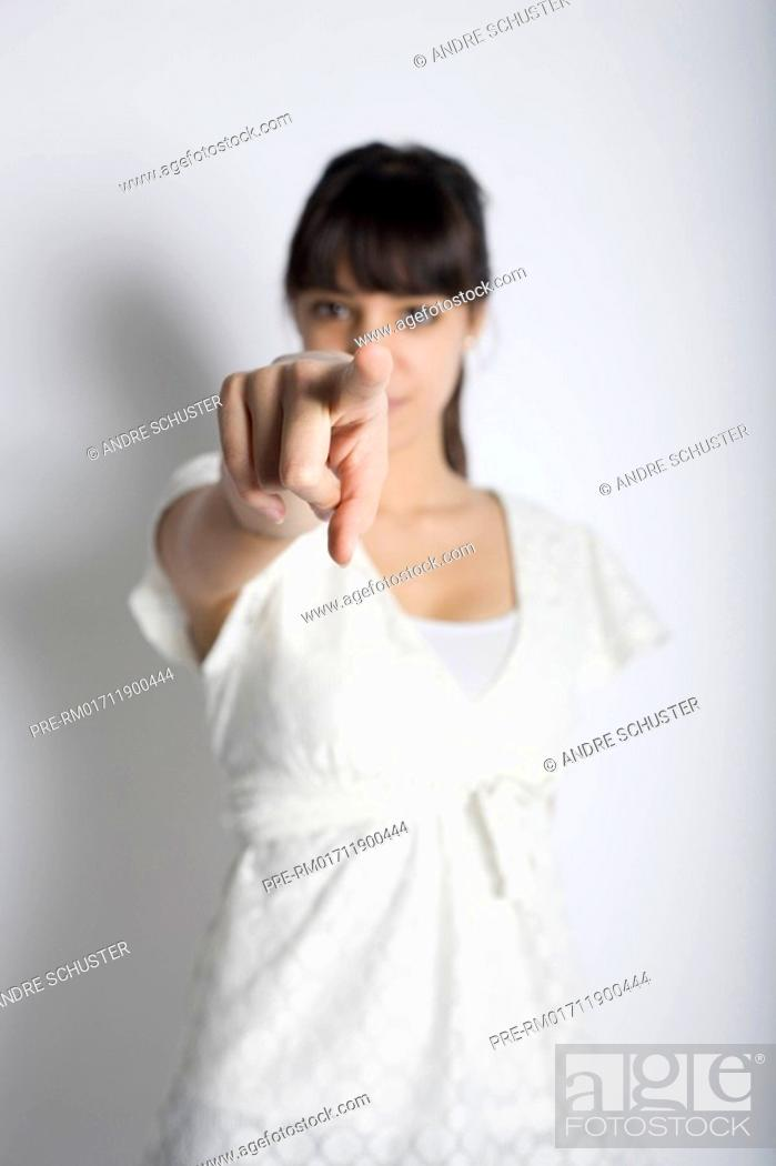 Stock Photo: Young woman pointing with her finger.