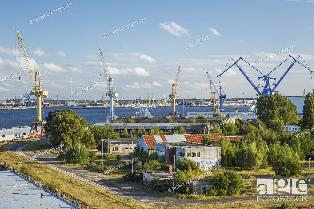Stock Photo: Warehouses and dock with yellow, blue and orange gantry cranes, Port of Warnemunde, Germany, Europe.
